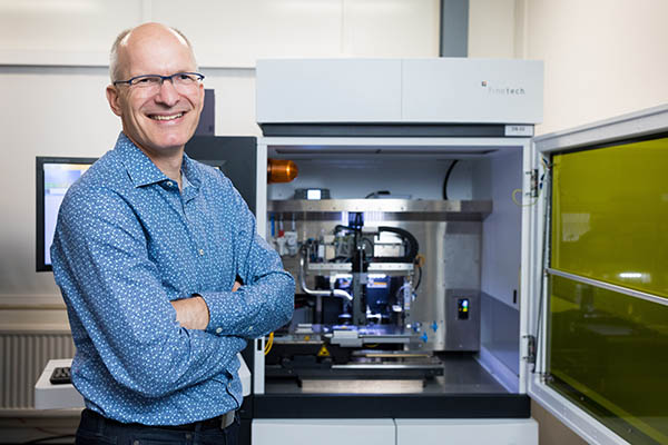 portrait of Erwin Vergeest with automated flip chip assembly machine